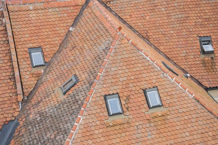 roof ridge: Closeup of new and old roof orange shingles with ridge tiles. windows on top of roof Stock Photo