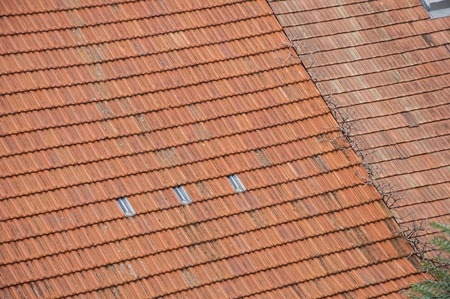 roof ridge: Closeup of new and old roof orange shingles with ridge tiles Stock Photo