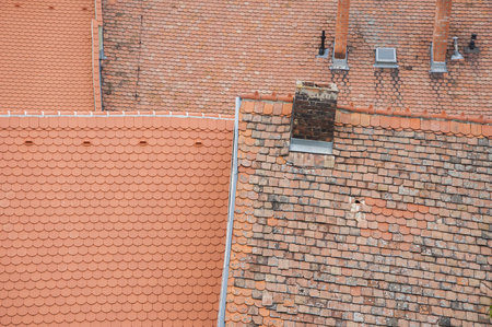 roof shingles: Closeup of roof orange shingles with chimney on top of roof.