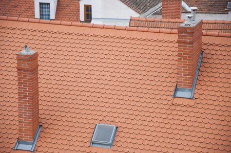 roof shingles: Closeuf of roof orange shingles with chimney on top of roof. Stock Photo