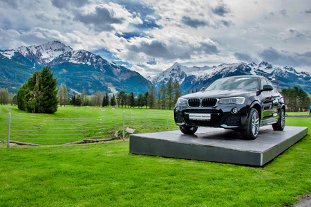 minsk: ZELL AM SEE, AUSTRIA, 15.4.2016 - Luxury BMW X6 on pedestal in Golf club Kaprun Zell am See. Black BMW on green of golf course with Alps in background