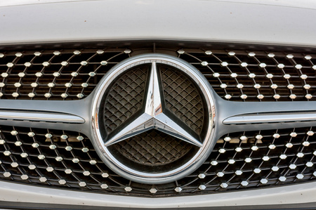 PRAGUE, THE CZECH REP., NOVEMBER 27, 2016: Closeup of front mask with logo of luxury car white cabrio Mercedes-Benz C200 with red roof. Car parking in front of car store Daimler Editorial