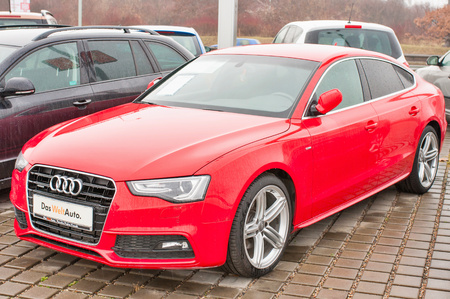 PRAGUE, THE CZECH REPUBLIC, 18.12.2016 - Closeup of new red car Audi A5 TDI quattro parking in front of car dealership Audi