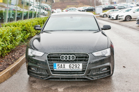 PRAGUE, THE CZECH REPUBLIC, 18.12.2016 - Closeup of new white car Audi A5 TDI quattro parking in front of car dealership Audi Editorial