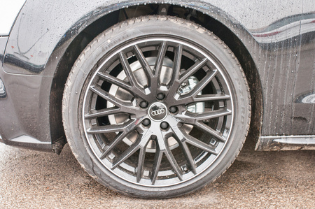 PRAGUE, THE CZECH REPUBLIC, 18.12.2016 - Closeup of car wheel new Audi quattro parking in front of car dealership Audi