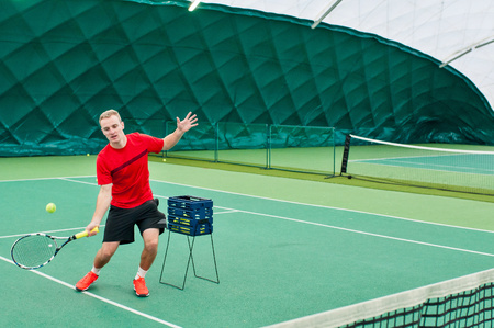 Closeup of professional tennis trainer dressed in red t-shirt, black shorts and red sport shoes. Tennis coach training tenis on court indoor. Stock Photo