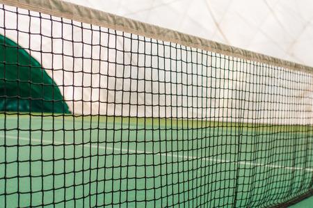 Tennis net indoor on tennis court, closeup view of tenis net with blurry background