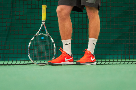 PRAGUE, THE CZECH REPUBLIC, 27.11.2016 - Tennis racquet Babolat and tennis player side by tenis net. Shoes and socks from Nike and racket and shorts from Babolat.