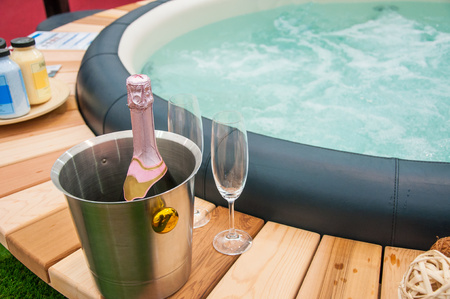 Detail view of luxury beautiful hot tub for relaxing, with decoration, towels, bottle of wine in nice interior. Stock Photo