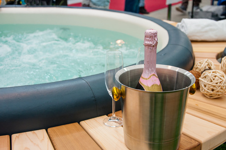 Detail view of luxury beautiful hot tub for relaxing, with decoration, towels, bottle of wine in nice interior. Zdjęcie Seryjne