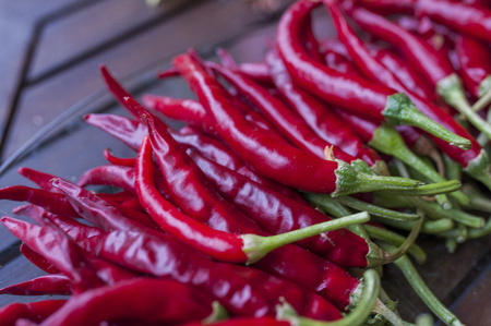 A lot of chilli peppers on wooden background. Hot red chilli pepper. Typical mexican food.