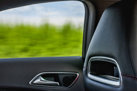 View from window of luxury car in high speed. Rear car window and closeup of luxury leather interior Stock Photo