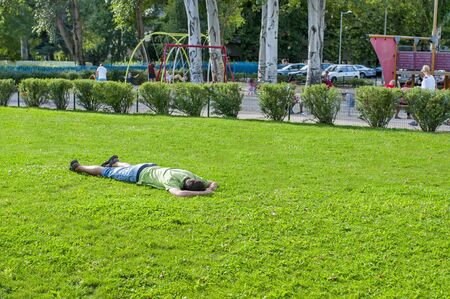 Man lying on grass and sleeping. Relaxing man lying on grass in summer Editorial