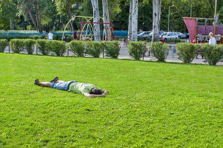Man lying on grass and sleeping. Relaxing man lying on grass in summer 新闻类图片