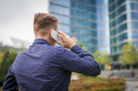 Calling young businessman, casual dressed. Man holds phone in hand and calling. Sharp looking fashion model.
