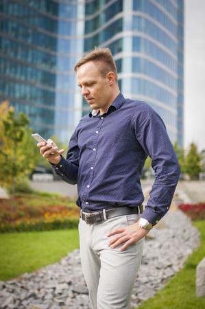 Anrufen junger Geschäftsmann, lässig gekleidet. Mann hält Telefon in der Hand und benennt. Scharfes schauendes Mode-Modell. Standard-Bild - 89534128