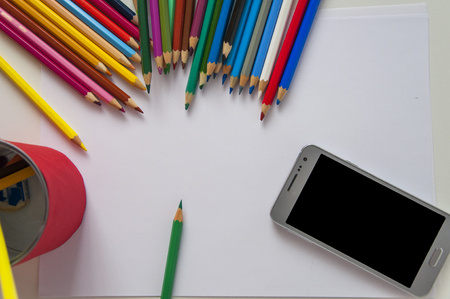 Closeup pencils and phone. Top view of workplace with colored pencils, paper and smartphone. Stock Photo