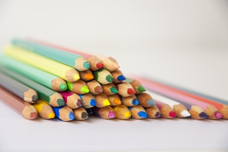 Colored pencils on isolated background. Closeup of colored pencils with a lot of colors. Front view.