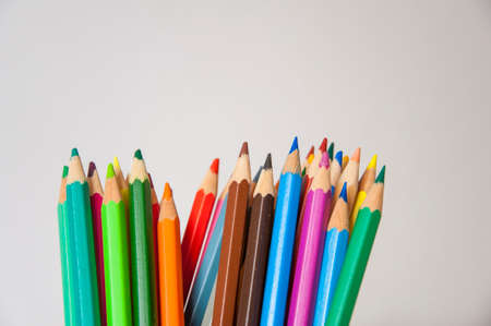 Colored pencils on isolated background. Closeup of colored pencils with a lot of colors. Stock Photo