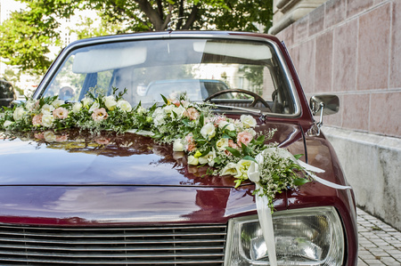 Decorated wine color wedding veteran car with flowers over the hood. Detail front view of wedding car