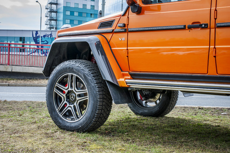 PRAGUE, THE CZECH REPUBLIC, 24.3.2018 - Closeup of wheel of Mercedes Benz G500 4x4 orange color in front of Car store Mercedes in Prague. G500 parked by the road