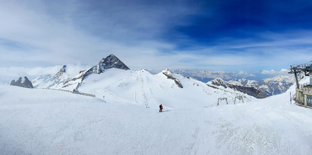 Winter panorama of Austrian Alps. Panorama photo of Austrian ski slopes, snowy peaks with blue sky and white clouds.