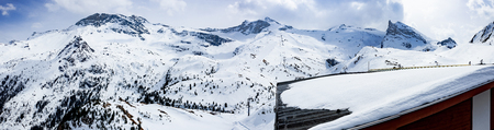 Panorama photo of Austrian ski slopes, snowy peaks with blue sky and white clouds. Winter panorama of Austrian Alps.