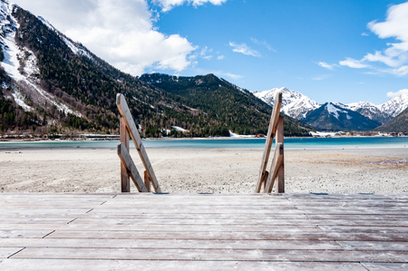 Wooden Pier on the lake between mountains in spring. Wooden jetty on the lake Achensee in Austira. Imagens