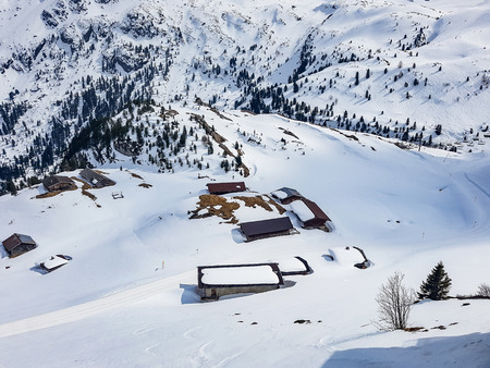 Beautiful wooden chalets in Alps in winter. Top view to wood cottage with a lot of snow all around. Austrian Alps