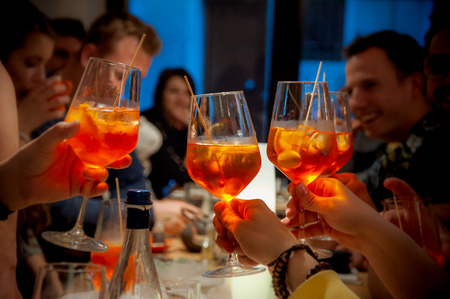 Group of friends cheers with aperol spritz in restaurant. Italian wine-based cocktail. Imagens - 122582224