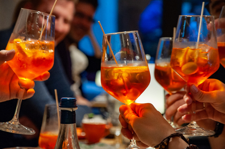 Group of friends cheers with aperol spritz in restaurant. Italian wine-based cocktail. Imagens - 122582327