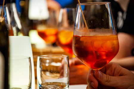 Man holds  cocktail in hand. A Spritz Veneziano, also called just Spritz or just Veneziano, is an Italian wine-based cocktail, commonly served as an aperitif in Northeast Italy