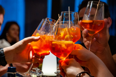 Group of friends cheers with aperol spritz in restaurant. Italian wine-based cocktail. Stock Photo