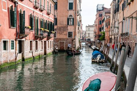 Venice, Italy, 22.4.2019: cruising Gondola in Venice canals between buildings. Famous cityscape buildings. rear view to Gondolier on gondola in channel Stok Fotoğraf - 128141056