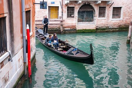 Venice, Italy, 22.4.2019: cruising Gondola in Venice canals between buildings. Famous cityscape buildings. rear view to Gondolier on gondola in channel