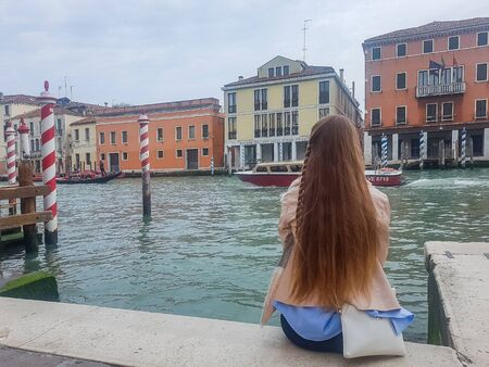 Venice, Italy, 22.4.2019: Sitting young lady in Venice on the pier with view to famous architecture 報道画像