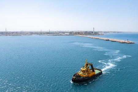 Cruising escort ship at sea. Top view of pilotage service boat cruising into harbor.