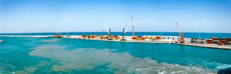 Porto di carico con molti contenitori. Grande porto mercantile, con poche gru e navi nel porto.