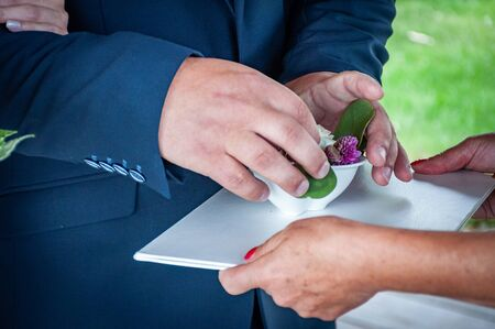 Closeup of giving wedding rings.