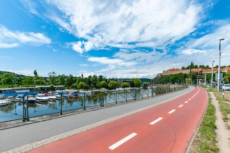 Bicycle path next to river Vltava in Prague. Summer cityscape of Prague with Vysehrad Castle in background. 写真素材