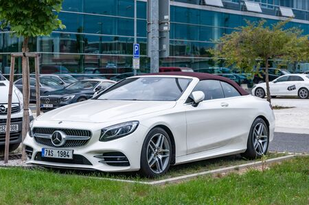 Prague, The Czech Republic, 1.9.2019: Luxury Mercedes Benz coupe cabrio with red roof parked in front of  car dealership Mercedes Benz. Front view