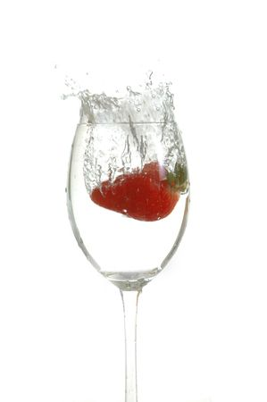 strawberry drop into glass with water photo