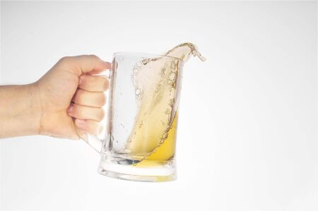 skoal: hand holding beer in glass close up Stock Photo