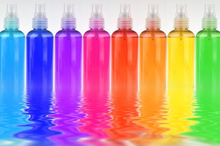 many colored bottles with cosmetics in a row reflecting in water Stock Photo