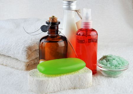 different cosmetics for body and  towel on  white photo