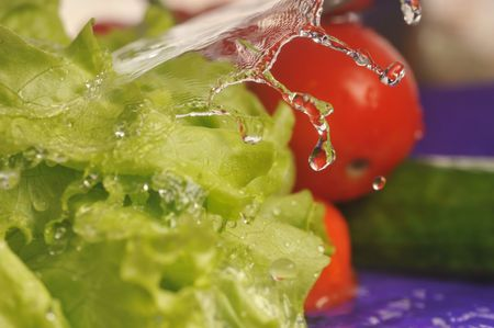 tomatoes, cucumber, salad and splashes on  violet background photo