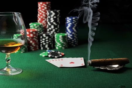 gambling counter: Cigar, chips for gamblings, drink and playing cards on green