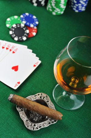 Cigar, chips for gamblings, drink and playing cards on green photo