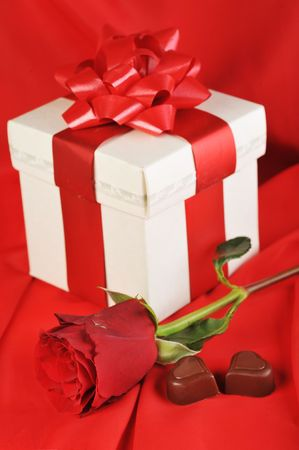 goodies: beautiful red rose, gift and chocolate  on red close up