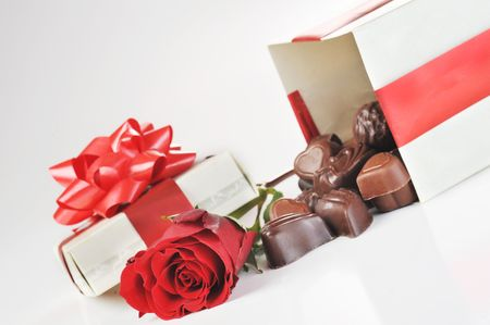 beautiful red rose, gift and chocolate  close up photo